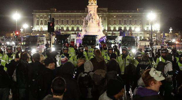 Police line up as protesters demonstrate outside Buckingham Palace during the Bonfire of Austerity protest.