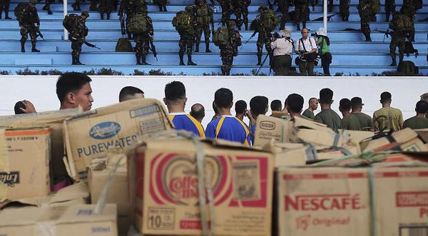 Soldiers stand near relief supplies for victims of Typhoon Haiyan at Villamor Airbase in Manila (AP)