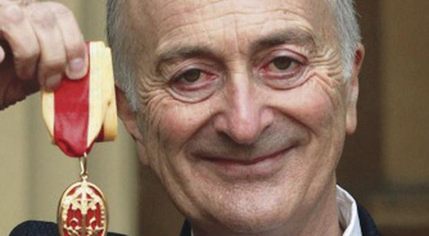 Sir Tony Robinson holds his medal after being knighted