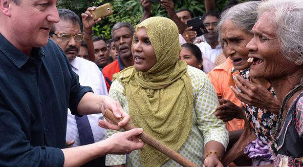 David Cameron meets Tamil refugees in the welfare village of Sabapathopillaia, in northern Sri Lanka, who were made homeless during the 26 year long civil war.