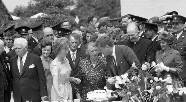 US president John F Kennedy stoops to have a word with hostess Mary Ryan at a tea party in the yard of her farm at Dunganstown, New Ross, Co Wexford