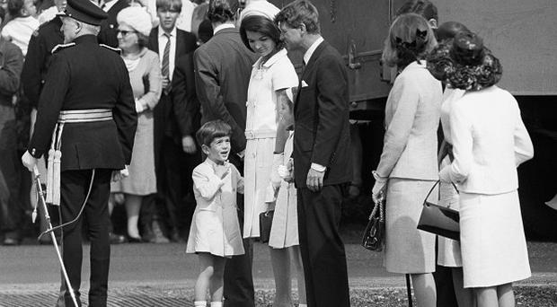 John Kennedy junior talks with his uncle, Senator Robert Kennedy, while waiting with his mother, Jacqueline Kennedy, and sister Caroline, to meet Queen Elizabeth II at the John F Kennedy Memorial site at Runnymede.