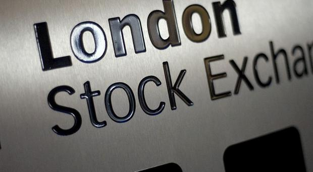 London's FTSE 100 closes lower in sluggish trading, despite new all-time highs on Wall Street.
