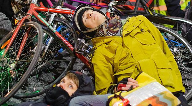 Cyclists take part in a 'die-in' protest outside the headquarters of Transport for London, in Blackfriars, London, calling for action to improve safety