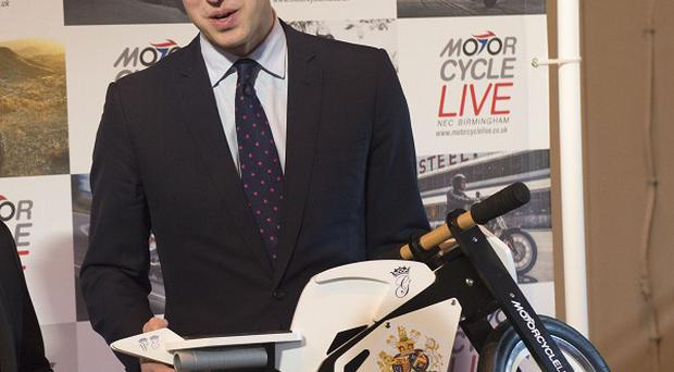 The Duke of Cambridge receives a gift for his son Prince George from exhibition director Dean Linehan (not pictured) during his visit to Motorcycle Live at the NEC, Birmingham.