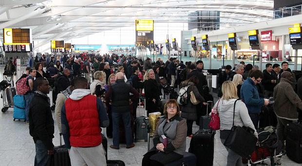 Passengers queue at Terminal 5 of Heathrow Airport after a 'technical problem' at the National Air Traffic Services control centre