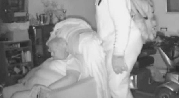 CCTV footage showing burglar Patrick Reid, 51, raiding the home of pensioner Margaret Woodward, 68, as she naps in an armchair at her home in Long Eaton, Derbyshire.