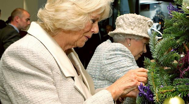 The Queen and the Duchess of Cornwall place baubles on a Christmas tree at the new Barnardo's headquarters in Ilford
