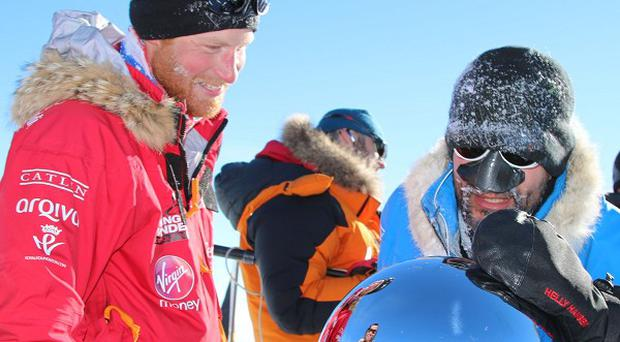 Prince Harry and another member of the Walking With The Wounded trek touch the pole, as they and their fellow adventurers reached the South Pole