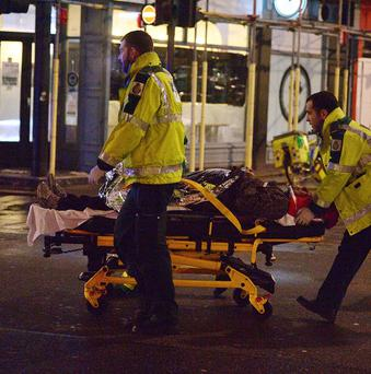 Paramedics attend to an injured person at the scene at the Apollo Theatre in Shaftesbury Avenue, central London