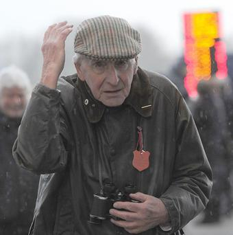 A racegoer shelters from the wind and rain at Wetherby Racecourse.