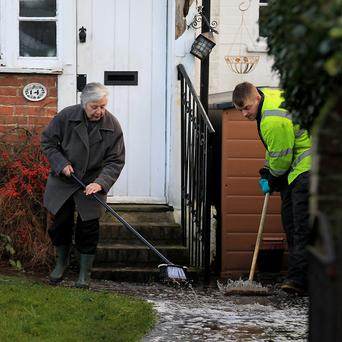 A local resident helps workmen clear water from her home in Yalding, Kent, after it was flooded during the recent bad weather.
