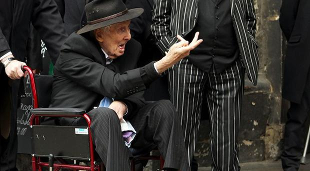 Ronnie Biggs gestures to the waiting press at the funeral of Bruce Reynolds, the mastermind behind the Great Train Robbery of 1963, at St Bartholomew The Great church in Smithfield, London.