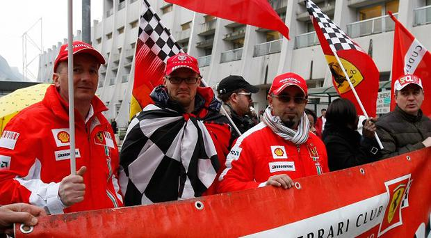 Supporters of Michael Schumacher hold Ferrari flags to mark his 45th birthday in front of the Grenoble hospital where he is being treated. (AP)