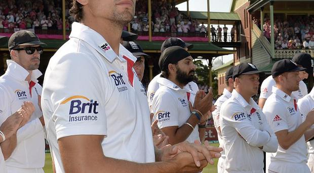 England captain Alastair Cook and his players look on as Australia are presented with the Ashes series trophy
