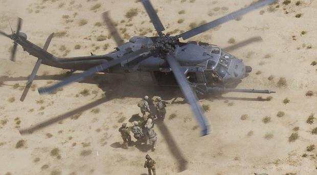 Two Afghan army soldiers, who were wounded in an explosion, are carried into a Pave Hawk in Afghanistan's Kandahar province. The helicopter has played a key role in US military and humanitarian aid missions.