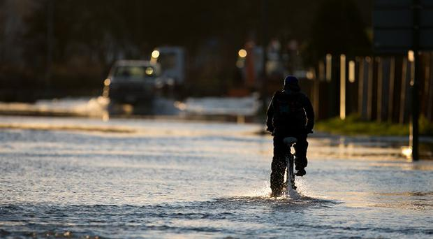 A man cycles down a flooded road in Chertsey, Surrey