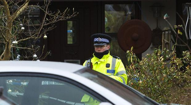 A police officer stands outside a house in Bosham, West Sussex, where a woman was found dead.