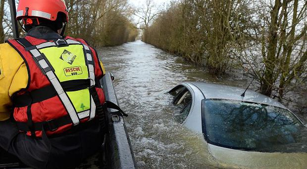 Members of the Avon and Somerset Police Underwater Search Unit inspect a submerged near Muchelney in Somerset