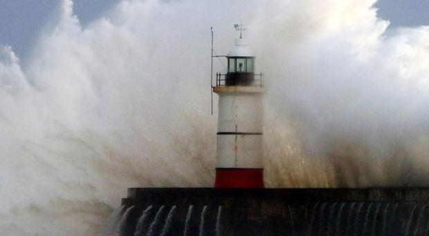 Waves crash over the harbour wall in Newhaven, Sussex