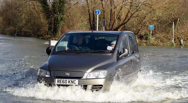 A car drives through flood water in Chertsey after the River Thames burst its bank