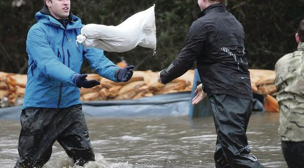 Princes William and Harry help with flood defences around Eton End School in Datchet, Berkshire, as more storms rattle the UK