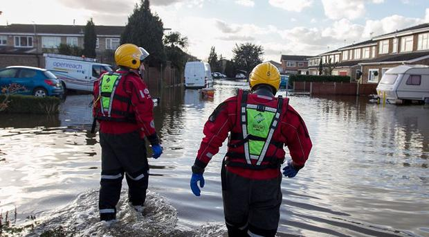 Members of the Surrey Fire and Rescue Service at a flood-hit housing estate in Staines-upon-Thames