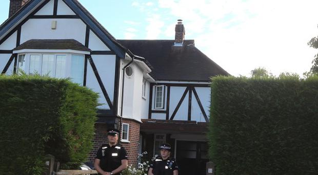 Surrey Police stand guard outside the home of Saad Al-Hilli in Claygate, Surrey, in 2012 after the family was shot dead in France