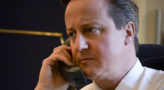 David Cameron talking on the telephone to US President Barack Obama about the crisis in Ukraine (Prime Minister's Office/PA)