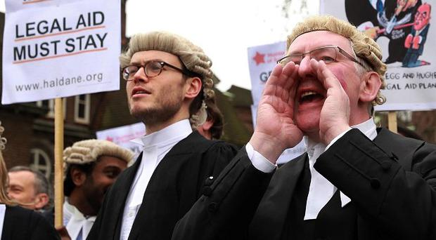 Lawyers from across the country marched on Westminster to protest against legal aid cuts and deliver a Magna Carta scroll to the Ministry of Justice