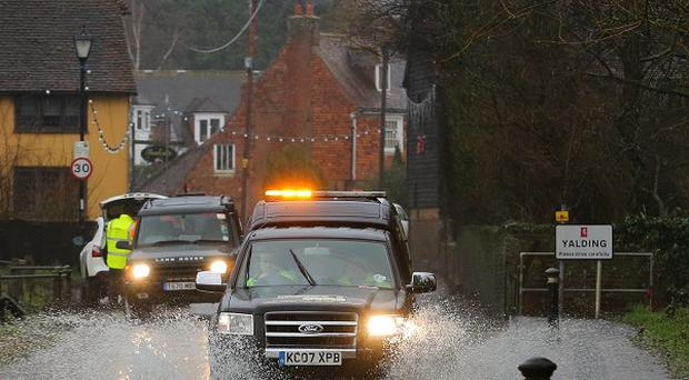 A car passes through a flooded road in Yalding, Kent