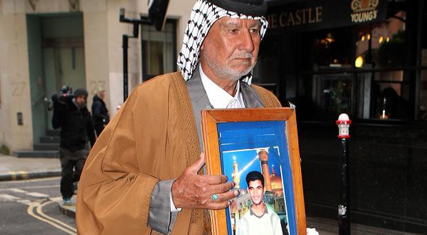 Mizal Karim Al-Sweady, the father of Hamid Al-Sweady carries a photo of his son after leaving the inquiry into his death.