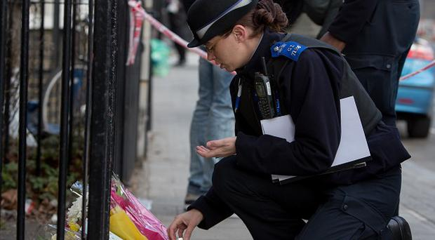 A police community support officer lays flowers handed to her at the scene in Eastway, Hackney, east London, where Shereka Marsh, 15, died after a shooting.