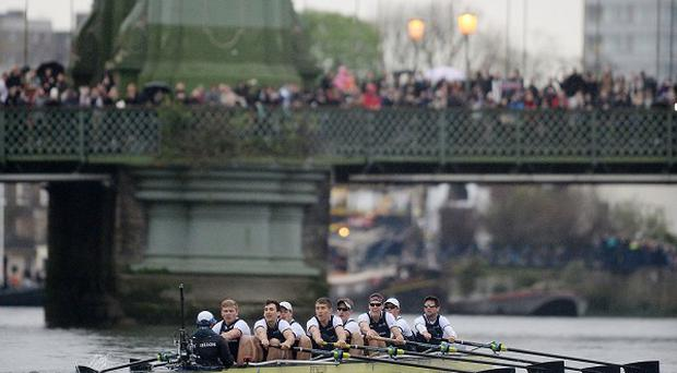 Oxford pass under Hammersmith Bridge during the Boat Race on the River Thames