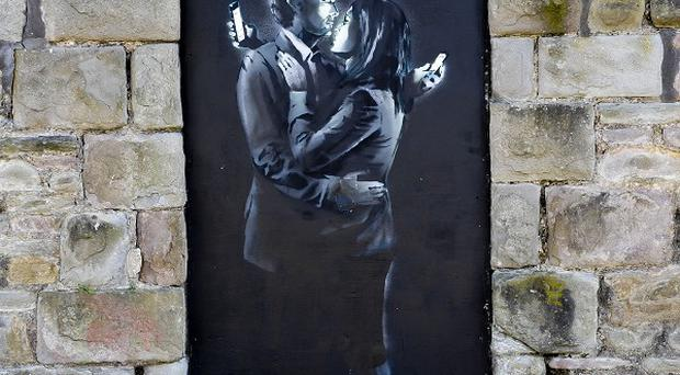 The latest officially confirmed Banksy artwork, named Mobile Lovers, before it was removed from a wall on Clement Street in Bristol