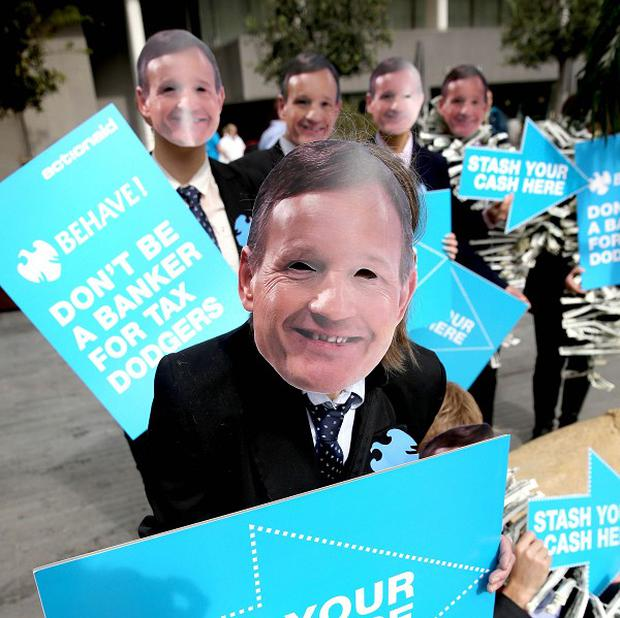 ActionAid campaigners wear masks featuring the face of Barclays boss Antony Jenkins as they protest at the bank's annual general meeting