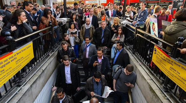 People queue outside Oxford Circus underground station, in central London, during the evening rush hour as the Tube strike continues