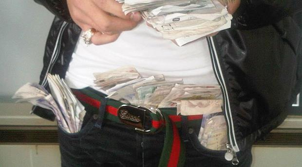 Russell Turner, 18, is shown posing for a photo with handfuls of cash and notes stuffed into his waistband and pockets (West Midlands Police/PA Wire)