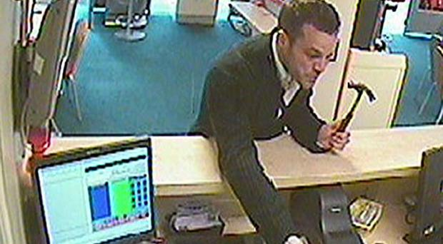 A CCTV still issued by police of an armed robber threatening a betting shop employee in Boscombe in Bournemouth (Dorset Police/PA)