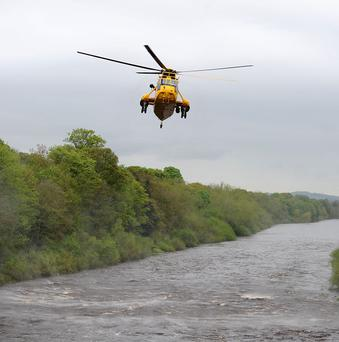 A RAF Sea King Helicopter flies over the River Tyne at Riding Mill, Northumberland where a group of kayakers went missing
