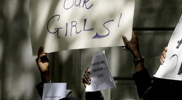 Demonstrators hold banners as they protest about the kidnapping of girls in Nigeria near the Nigerian High Commission in London (AP)
