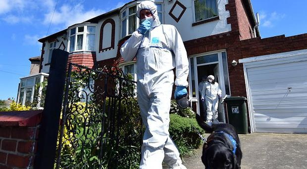 A forensic officer with a dog outside a house in North Shields which is being searched by police