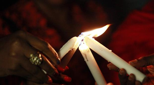 People light candles during a vigil in Abuja to mark one month after the Nigerian schoolgirls were kidnapped (AP)