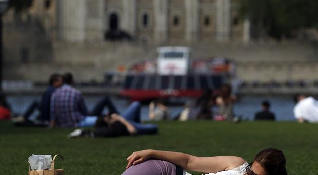 Visitors to the park next to London's City Hall enjoy the sun