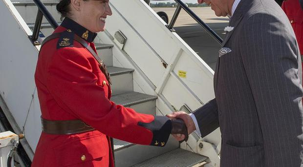 The Prince of Wales shakes hands with Canadian protection officer, Police Inspector Marie-Claude Cote on departure from RAF Brize Norton in Oxfordshire