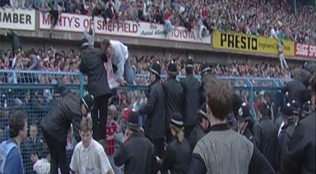 People climbing over the fence at the Leppings Lane end of Hillsborough Stadium as the tragedy unfolded