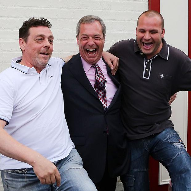 Ukip leader Nigel Farage celebrates his party's gains with two supporters during a visit to Basildon, Essex