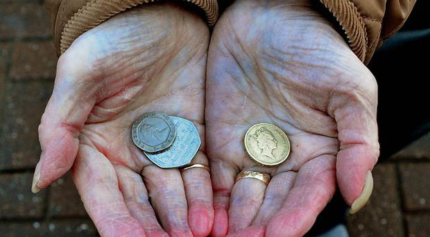 A pensioner holds some change in her hand.