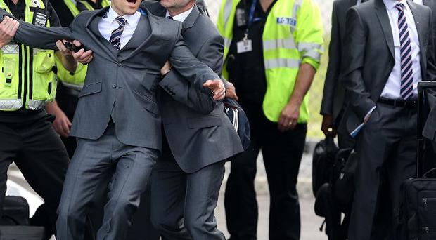 Comedian Simon Brodkin is taken away from the England team by security at Luton Airport, Luton.