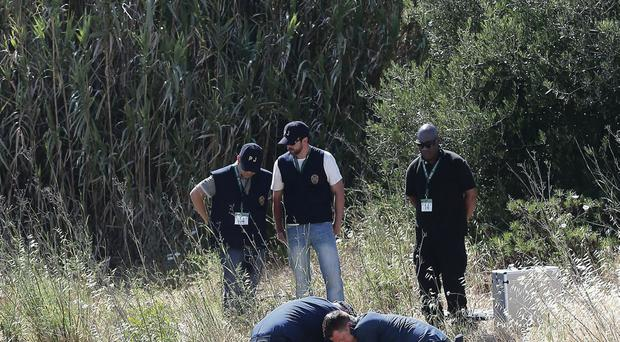 British police sift through soil on an area of wasteland in the town of Praia da Luz in Portugal, where Madeleine McCann went missing in May 2007